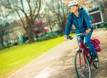 Woman riding a bike through a park