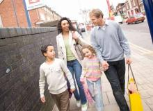 Family walking from the station to a bus stop