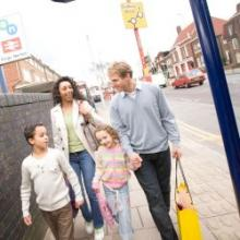 Family walking past train station and bus stop