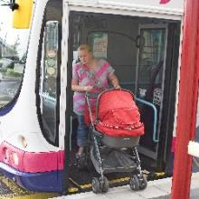 Woman getting off bus with pram, West Yorkshire